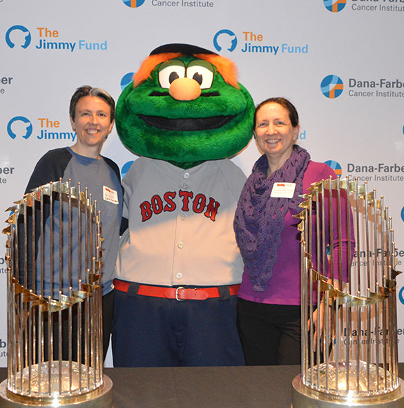 Two Rally team captains with Red Soxm mascot Wally and two World Series trophies