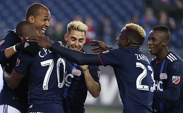 New England Revolution players celebrating during a game